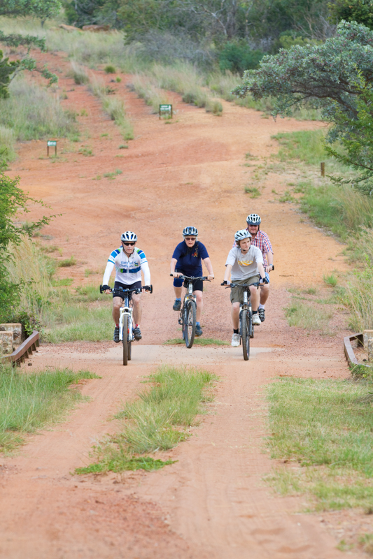 A small group of cyclists enjoy go game viewing on their mountain bikes.